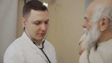 dövmek : Doctor listens heart of senior man with stethoscope
