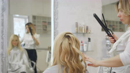 curling hair : Hairdresser curls blonde hair with curling iron
