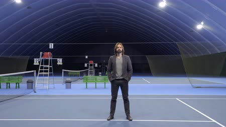 освещать : Businessman at the tennis court in the dark Стоковые видеозаписи
