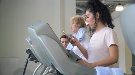 strong granny : Pretty brunette uses phone walking at the treadmill