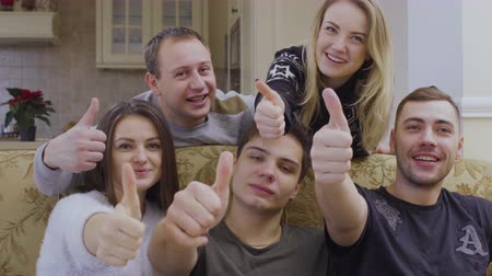 пять : Five young caucasian friends looks at camera and shows thumbs up