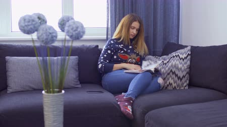 periódico : Beautiful young girl wearing sweater is relaxing on sofa with journal