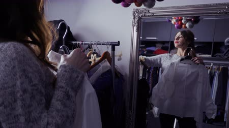 решить : Young beautiful girl looks at the mirror and choosing clothes for special event