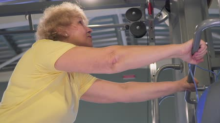 strong granny : Elderly woman stretching near simulator in the gym