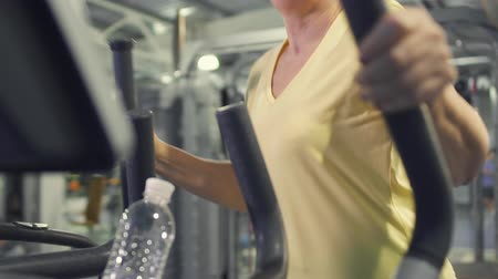 strong granny : Senior woman makes exercises for legs on simulator in the gym Stock Footage