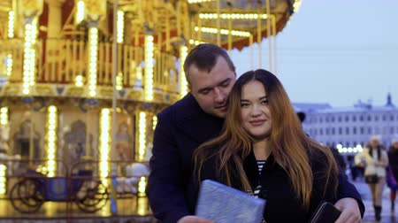 atender : Handsome man meets with his wife near the carousel in amusement park
