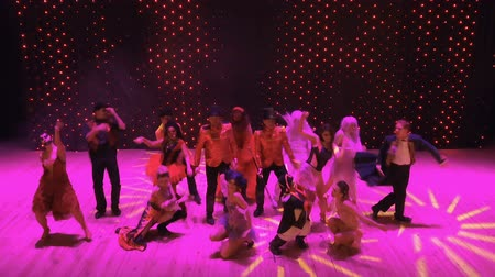greasepaint : Crazy people dances in colorful lights at stage in modern theatre Stock Footage