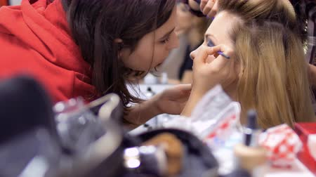 greasepaint : Professional make-up artist and hairdresser prepares woman to the performance Stock Footage