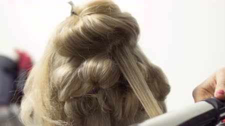 tongs : Hairdresser makes hairstyle with curling iron to woman Stock Footage