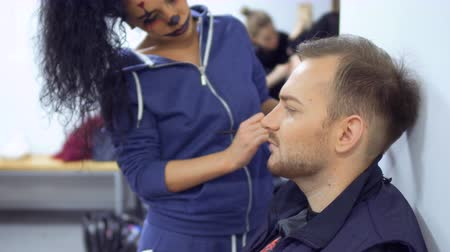greasepaint : Woman with horrible greasepaint on face help colleague and makes make-up for him Stock Footage