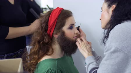 greasepaint : Stylists sticks artificial beard on girls face, dressing room in theatre