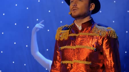 rol : Young handsome man in red tail-coat sings on the stage in theatre Stok Video