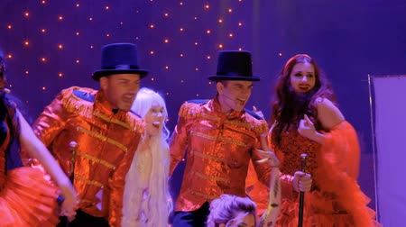 greasepaint : People in bright costumes sings song on colorful stage in theatre Stock Footage