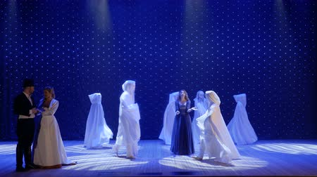 rendkívüli : Beautiful woman dances with strangers in cloaks on the stage in theatre
