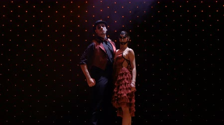 greasepaint : Couple wearing scenic costumes posing for camera on stage in light of spotlight