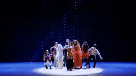 rendkívüli : People dressed in scenic costumes are dancing on stage in theatre