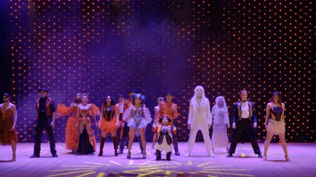 песня : Different heroes in scenic costumes are dancing in theatre