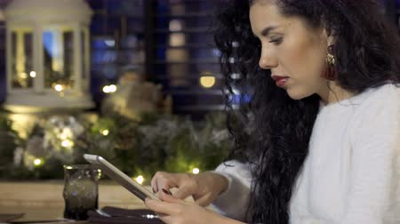 e book : Young beautiful brunette uses digital tablet in cafe Stock Footage