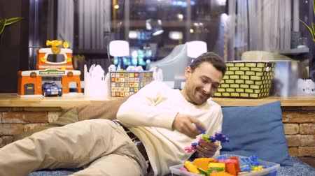 pillow block : Young funny man plays with constructor in childrens room in cafe