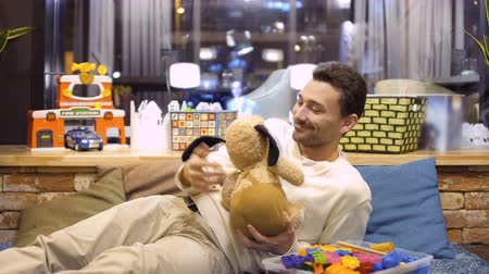 peluş : Adult caucasian man plays with toy dog in the childrens room in cafe