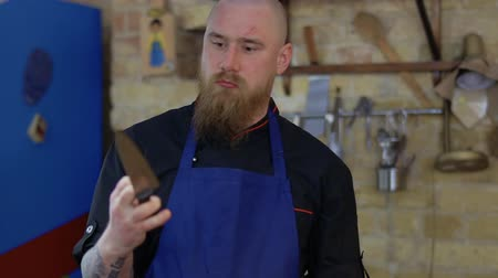 ciddi : Portrait of serious chef with scars on face and with knife in hands