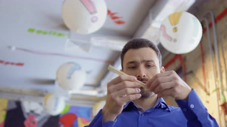 closing : Young funny guy closes nose with chinese chopsticks because of bad smell Stock Footage