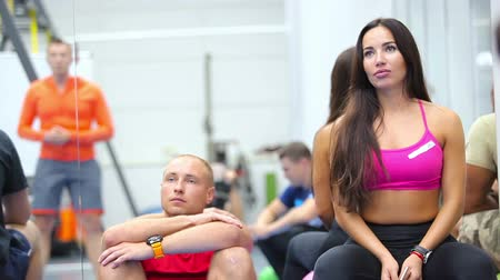 listener : Beautiful woman and young man listening a coach on the training in the gym Stock Footage