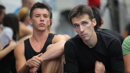 listener : Two attractive men listening a coach on the training in the gym