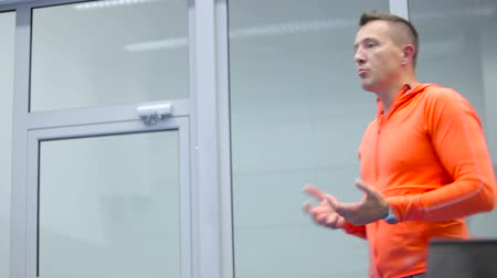 antrenör : The trainer in orange costume talking with audience on the training Stok Video