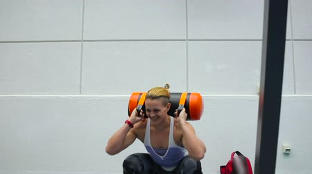 squatting : Sportswoman squats with weighting in the gym