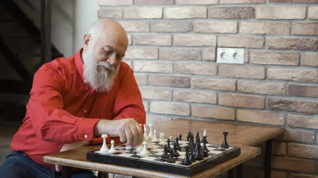 šachy : Senior gray-haired man play chess with himself