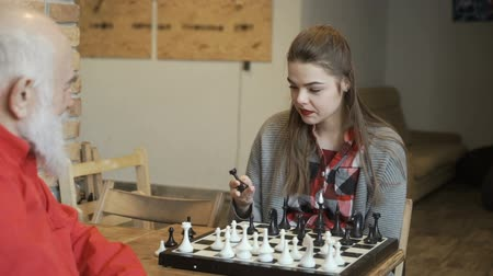 piskopos : Young girl asks her grandpa how to play chess Stok Video