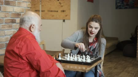 piskopos : Young girl plays chess with grandfather