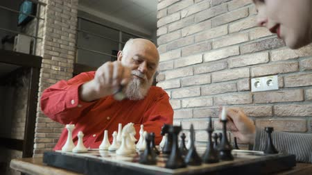 piskopos : Senior man play chess with granddaughter at home