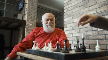 епископ : Old man play chess with granddaughter