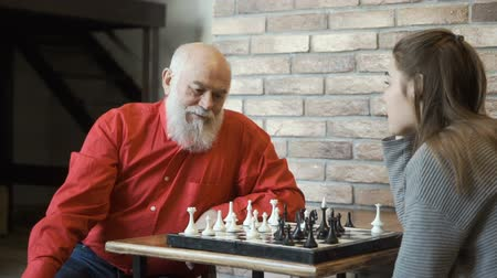 rycerze : Grandfather teaches granddaughter to build strategy during the chess game