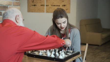 piskopos : Grandpa with granddaughter play chess Stok Video