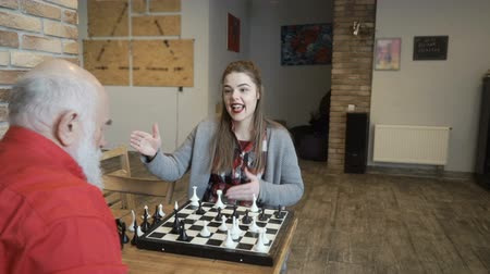 rainha : Young girl win a game of chess in her grandfather