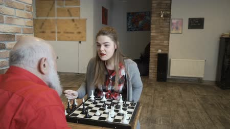 rytíř : Happy girl talks with grandfather after successful chess game