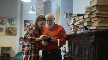 investigador : Gray-haired grandfather and granddaughter read interesting book together