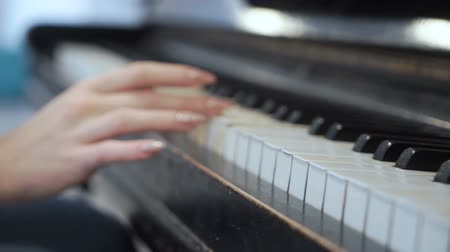 zongora : Female hand gently touches piano keys