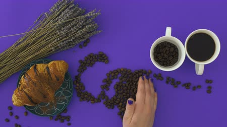 croissants : Female hand creates word coffee from coffee beans