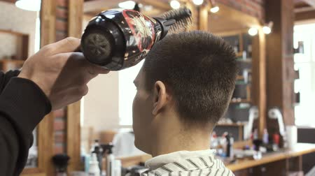промывали : Hairdresser dries guys hair with hairdryer in barbershop Стоковые видеозаписи