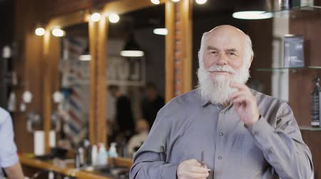 восхищенный : Mature man twists his mustache and posing for camera in barbershop Стоковые видеозаписи
