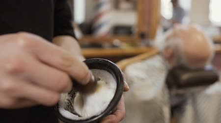 борода : Hairstylist mixes shaving cream with brush Стоковые видеозаписи