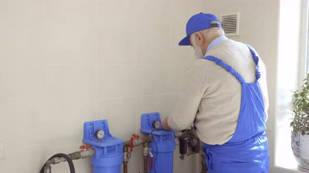 professionally : Senior man repair heating pipes in blue overalls