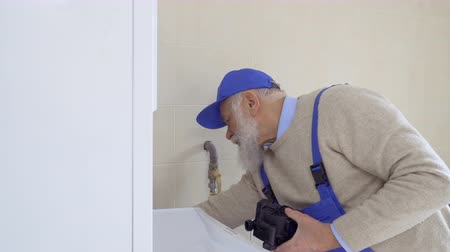 professionally : Senior gray-haired man wearing coveralls repairs boiler