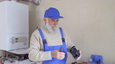 kotel : Elderly man wearing blue overalls holds plastic part from pipe in hands Dostupné videozáznamy