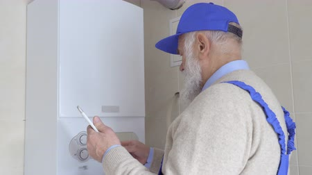 professionally : Old master adjust boiler temperature with digital tablet