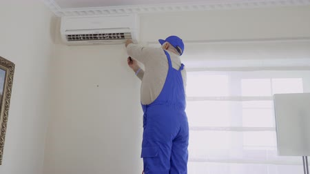 şartlar : Professional mature master installs the air conditioning in the room Stok Video